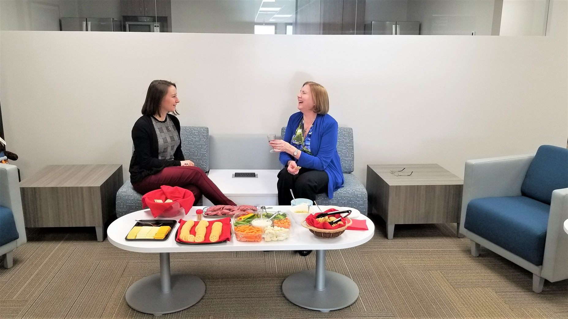 Dawn Benchelt and Anna Kuta enjoy the new IMC updated community space. Renovations were completed to the team's space early this year, featuring a new kitchen, open-floor plan, new collaboration rooms, and a new conference room.